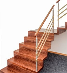 Da diese gerade Faltwerktreppe als Podesttreppe gebaut ist, kann sie sich förmlich in die Ecke des Wohnraums schmiegen. Die dunkle Holzfarbe bietet einen schönen Kontrast zu den Farben der Wände und unterstreicht perfekt die Faltung der Treppe. Auch das dezent moderne Geländer harmoniert vollkommen mit dem Charakter dieser Faltwerktreppe.