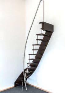 Eine Tragbolzentreppe ist eine perfekte Treppenbauart für eine Raumspartreppe, wie diese viertelgewendelte Raumspartreppe zeigt. An der geschlossenen Seite ist sie über die Wandwange mit Bolzen verankert. Die Trittstufen werden an der offenen Seite durch die Tragbolzen getragen. Deshalb kommt dem Geländer keine statische Funktion zu, so dass die Geländerform frei gewählt werden kann. Hier ermöglicht ein elegant geschwungenes Geländer, das nur aus einem Handlauf besteht, ein bequemes und sicheres Benutzen der Raumspartreppe.
