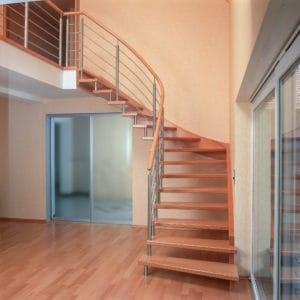 Diese Tragbolzentreppe ist über eine eingestemmte Wandwange mit der Wand verankert. An der offenen Seite unterstreicht das dezente Relinggeländer mit dem runden Handlauf aus Holz die leichte Architektur dieser freitragenden Treppe.