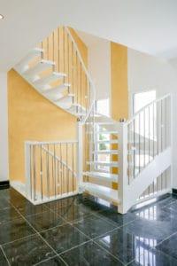 Sehr elegant sieht diese Tragbolzentreppe aus, die ganz in weiß in einem edlen Kontrast zur Farbe des Fußbodens und zur Farbe der Hauswand steht.