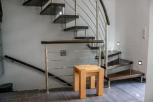 Das Geländer dieser Tragbolzentreppe betont mit seinen quadratischen Edelstahlpfosten das moderne Ambiente des Raumes.